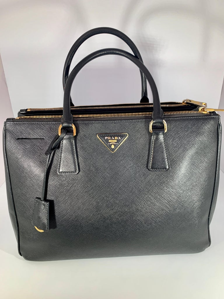 Prada Saffiano Lux Double-Zip Tote Bag, Black Boxy saffiano leather top handle bag with polished hardware and a removable crossbody strap. Double top handles Removable, adjustable shoulder strap Side-snap gussets Open top Goldtone hardware Two