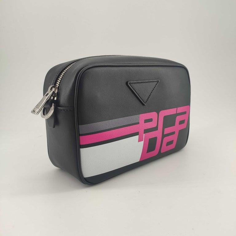 - Designer: PRADA - Condition: Never worn.  - Accessories: Dustbag, Authenticity Card - Measurements: Width: 22cm, Height: 15cm, Depth: 7cm, Strap: 112cm - Exterior Material: Leather - Exterior Color: Black - Interior Material: Cloth - Interior
