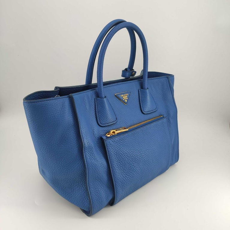 - Designer: PRADA - Condition: Very good condition. Sign of wear on base corners, Stain at the bottom of the bag - Accessories: Dustbag - Measurements: Width: 30cm, Height: 25cm, Depth: 15cm, Strap: 115cm - Exterior Material: Leather - Exterior