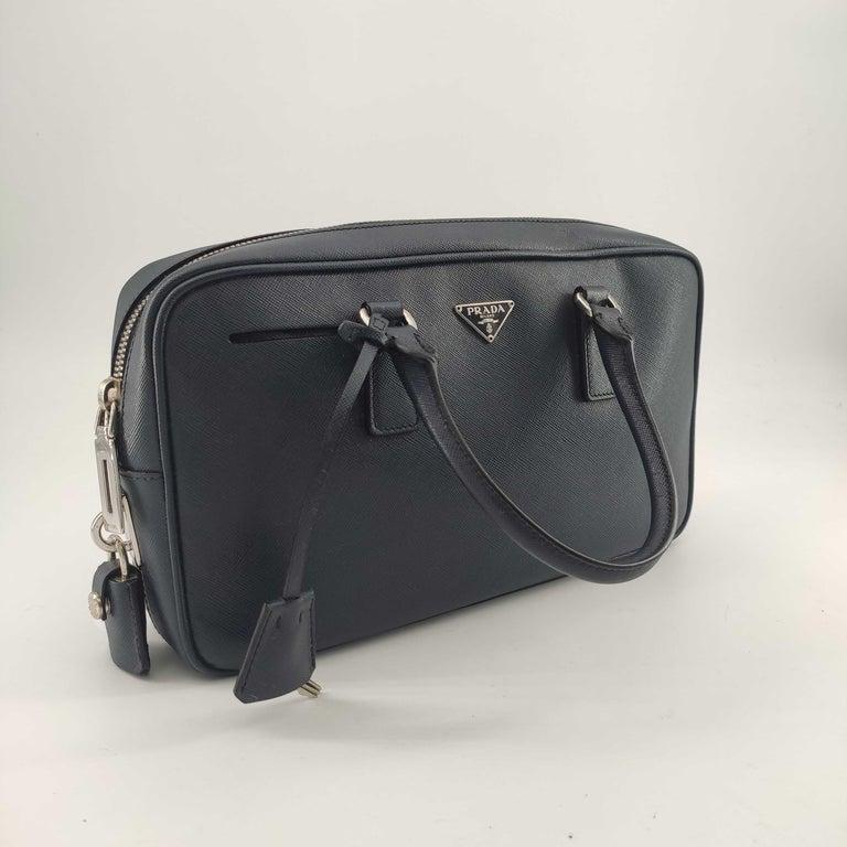 - Designer: PRADA - Condition: Very good condition.  - Accessories: Dustbag, Keys, Padlock - Measurements: Width: 28cm, Height: 16cm, Depth: 6cm - Exterior Material: Leather - Exterior Color: Blue - Interior Material: Cloth - Interior Color: Black -