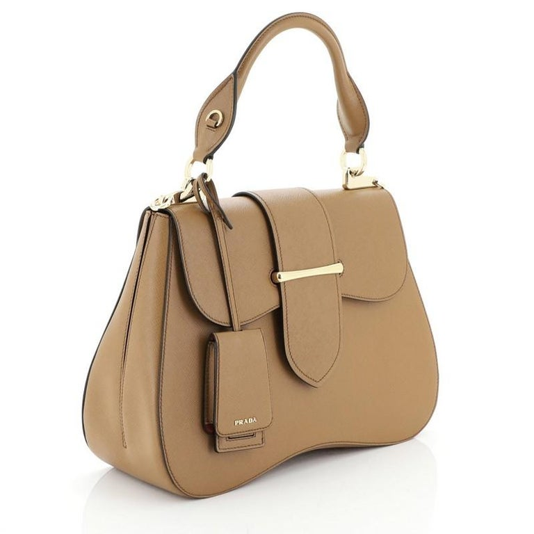 This Prada Sidonie Top Handle Bag Saffiano Leather Large, crafted from brown saffiano leather, features a rolled top handle and gold-tone hardware. Its flap opens to a red leather interior with side zip and slip pockets.   Condition: Excellent.