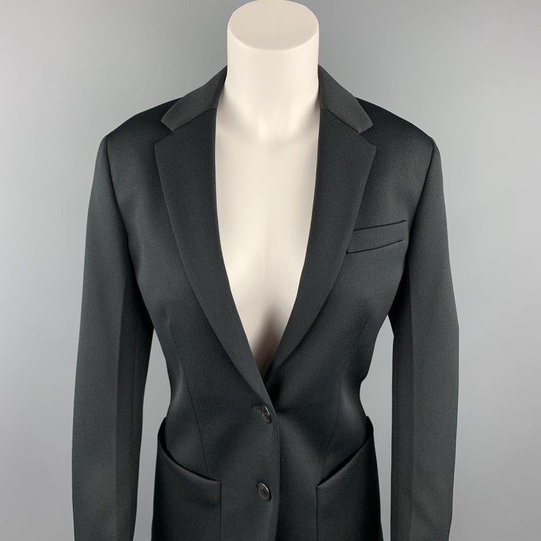 PRADA blazer comes in a black polyester with a full liner featuring a oversized fit, notch lapel, patch pockets, an a two button closure. Made in Italy.  New With Tags. Marked: IT 36  Measurements:  Shoulder: 15.5 in. Bust: 36 in.  Sleeve: 24 in.