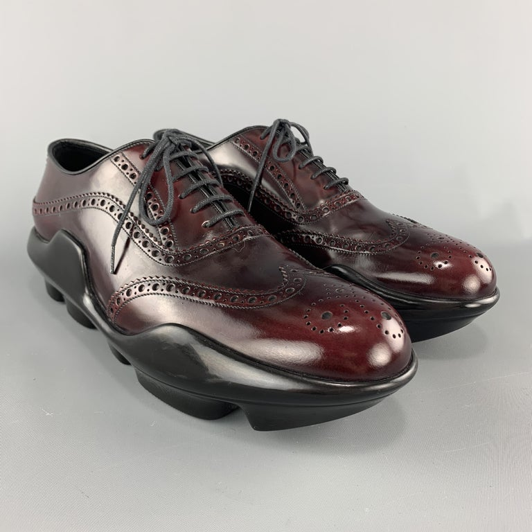 PRADA dress shoes come in deep burgundy antique effect polished leather with a wingtip, brogueing throughout, and exaggerated rubber platform sole. Made in Italy.  Very Good Pre-Owned Condition. Marked: UK 9  Outsole: 12.5 x 4.5 in.