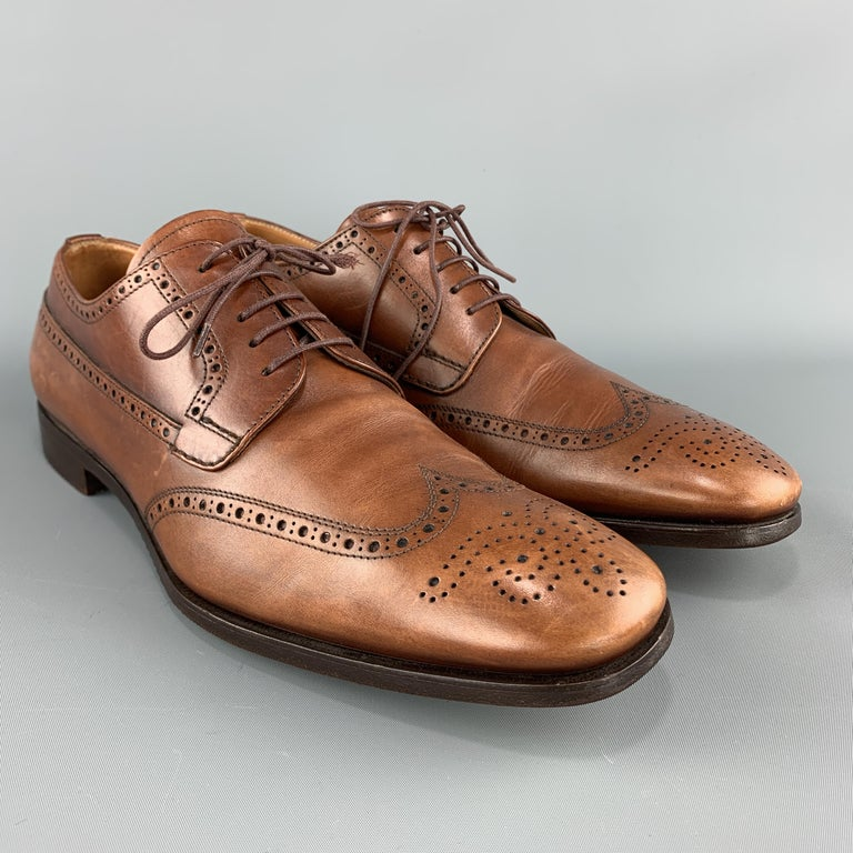 PRADA dress shoes come in tan leather with a wing tip, medallion, and perforated broguing throughout.  Made in Italy.  Very Good Pre-Owned Condition. Marked: UK 9.5  Outsole: 12.25 x 4.25 in.