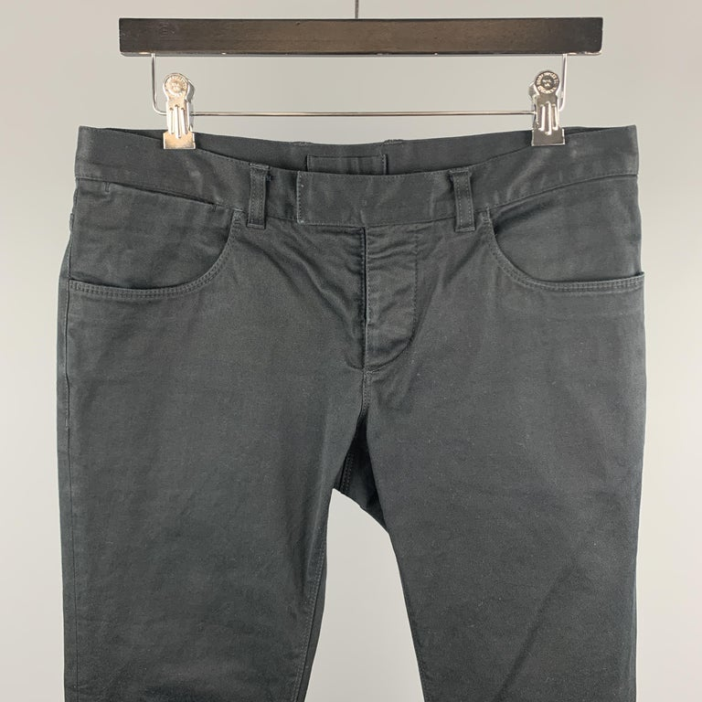 PRADA casual pants comes in a black cotton blend featuring a slim fit and a button fly closure.   Very Good Pre-Owned Condition. Marked: EU 48  Measurements:  Waist: 32 in.  Rise: 7.5 in.  Inseam: 32 in.