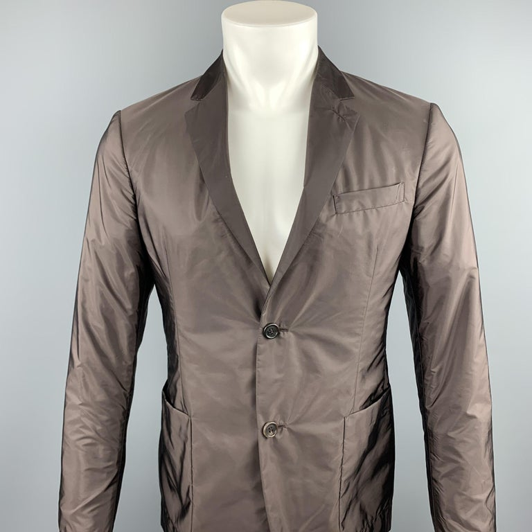 PRADA sport coat comes in a brown polyester featuring a notch lapel, patch pockets, and a two button closure.   Excellent Pre-Owned Condition. Marked: TG 48  Measurements:  Shoulder: 16.5 in.  Chest: 38 in.  Sleeve: 26 in.  Length: 28 in.