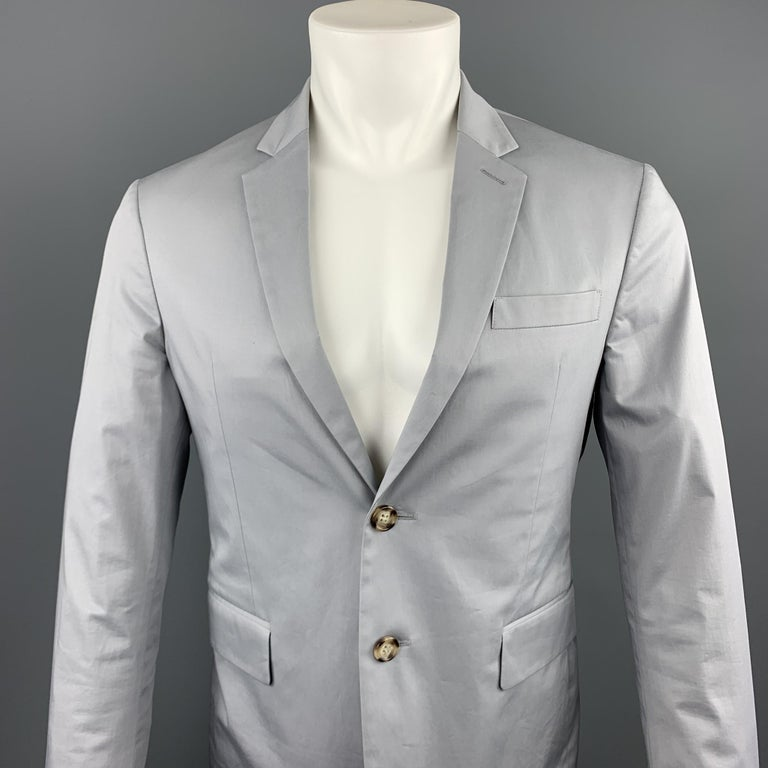 PRADA sport coat comes in a light gray cotton featuring a notch lapel, patch pockets, and a two button closure.   Excellent Pre-Owned Condition. Marked: 48  Measurements:  Shoulder: 16.5 in. Chest: 38 in. Sleeve: 26 in. Length: 28 in.