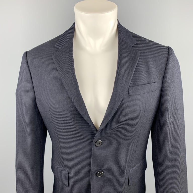 PRADA sport coat comes in a navy textured wool featuring a notch lapel style, flap pockets, and a two button closure.  Sleeves have been professionally altered / shortened.  Excellent Pre-Owned Condition. Marked: IT 48  Measurements:  Shoulder: 16.5