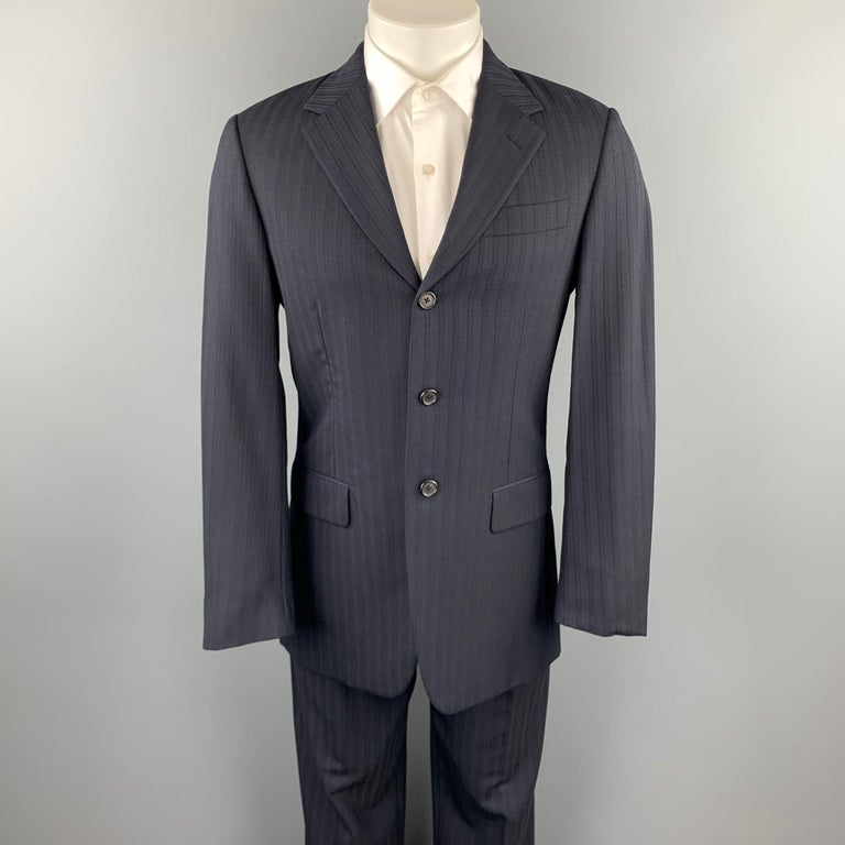 PRADA suit comes in navy stripe wool blend and includes a single breasted, three button sport coat with a notch lapel and matching flat front trousers. Made in Italy.  Very Good Pre-Owned Condition. Marked: IT 48 R  Measurements:  -Jacket Shoulder: