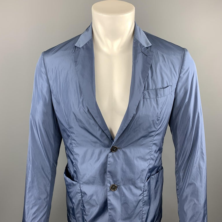 PRADA sport coat comes in a steel blue polyester featuring a notch lapel, patch pockets, and a two button closure.   Excellent Pre-Owned Condition. Marked: TG 48  Measurements:  Shoulder: 16.5 in.  Chest: 38 in. Sleeve: 26 in. Length: 28 in.