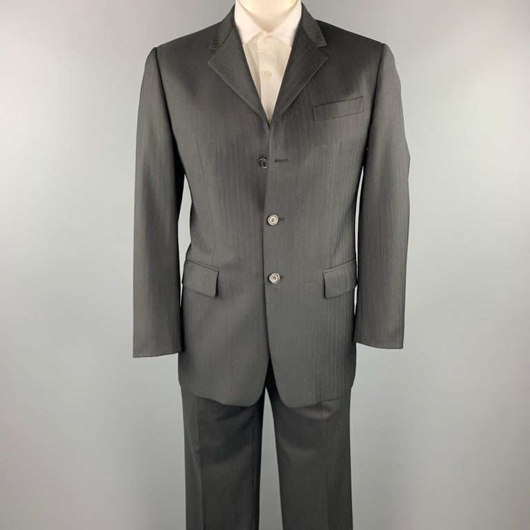 PRADA suit comes in a charcoal stripe virgin wool with a full liner and includes a single breasted, three button sport coat with a notch lapel and matching flat front trousers. Made in Italy.  Excellent Pre-Owned Condition. Marked: IT 50