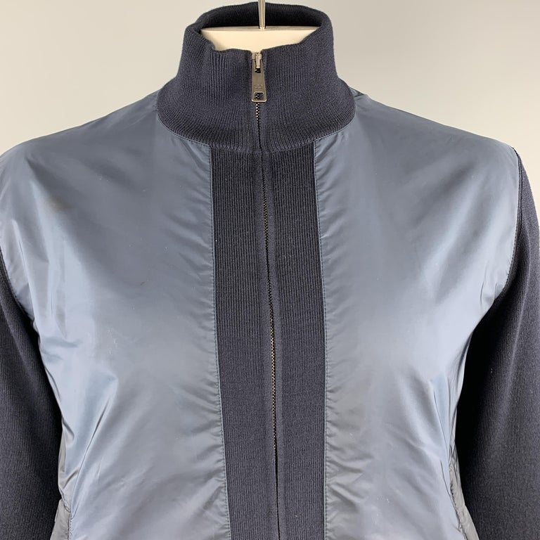 PRADA jacket comes in navy marino wool knit with a high collar, zip front, and nylon panels. Wear throughout. As-is. Made in Romania.  Good Pre-Owned Condition. Marked: IT 52  Measurements:   Shoulder: 18 in. Chest: 46 in. Sleeve: 28 in. Length: