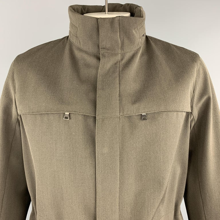 PRADA sport ski jacket come sin olive green wool blend woven fabric with a high zip out hood collar, zip up front with hidden snap placket, zip pockets, and elastic waist. Made in Romania.  Excellent Pre-Owned Condition. Marked: IT