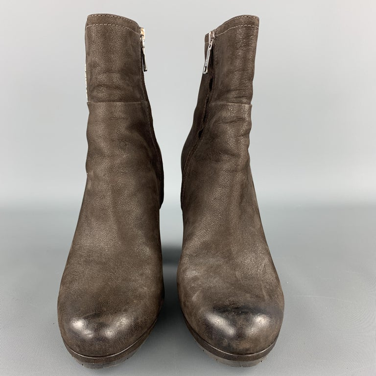 PRADA ankle booties come in textured brown leather with a silver tone logo shaft and chunky heeled sole.   Very Good Pre-Owned Condition. Marked: IT 37.5  Heel: 4 in. Length: 5 in.