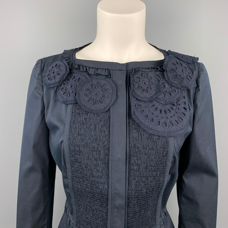 PRADA jacket comes in a navy cotton with eyelet details featuring a collarless, ribbon trim, ruffled detail, and a snap button closure. Made in Italy.  Very Good Pre-Owned Condition. Marked: IT 44   Measurements:  Shoulder: 15 in.  Bust: 34 in.