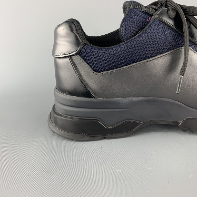 PRADA dress sneaker comes in gray and black leather with navy blue mesh panels, lace up front, and extended rubber sole with toe cap. Wear throughout. Made in Italy.  Very Good Pre-Owned Condition. Marked: UK 8  Outsole: 12.5 x 4.5 in.