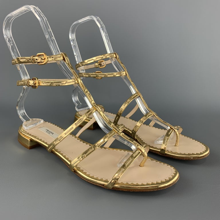 PRADA sandals come in metallic gold leather with T strap Gladiator style straps. Made in Italy.  Very God Pre-Owned Condition. Marked: IT 39.5  Outsole: 10.45 x 3.75 in.