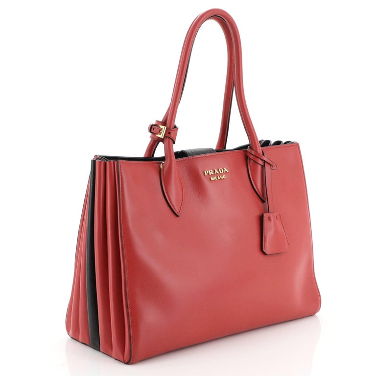 This Prada Soft Bibliotheque Handbag City Calfskin Medium, crafted from red calfskin leather, features dual rolled handles, accordion sides for expansion, and gold-tone hardware. Its magnetic closure opens to a black fabric and leather interior with