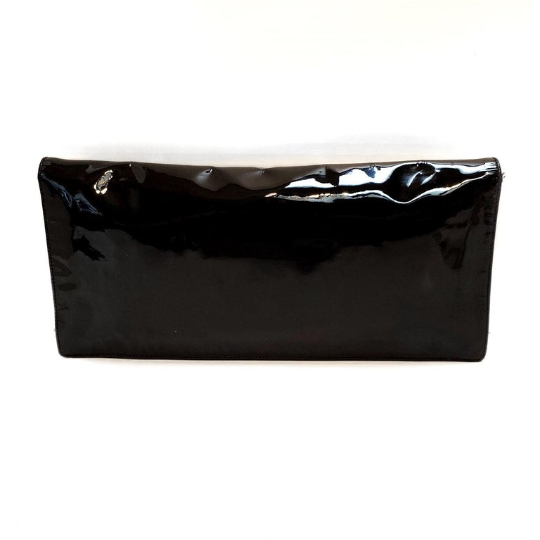 Brand - Prada Collection - Spazzolato Estimated Retail - $650.00 Style - Clutch Material - Patent Leather Color - Black Closure - Snap Hardware Material - Silvertone Size - Small Feature - Inner Pockets Accent - Mirrored Tag Product Line - Prada