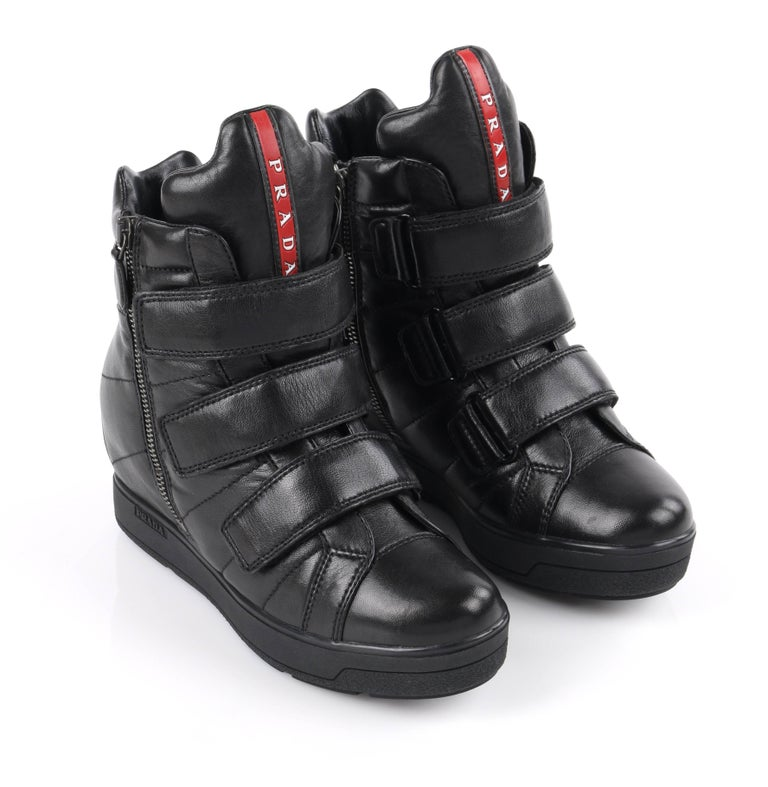 Prada Sport Autumn / Winter 2013 black vitello leather triple strap hi top wedge sneakers. Designed by Miuccia Prada. Black smooth vitello leather upper. Three adjustable hook and loop straps across front. Two gun-metal toned side seam zippers with