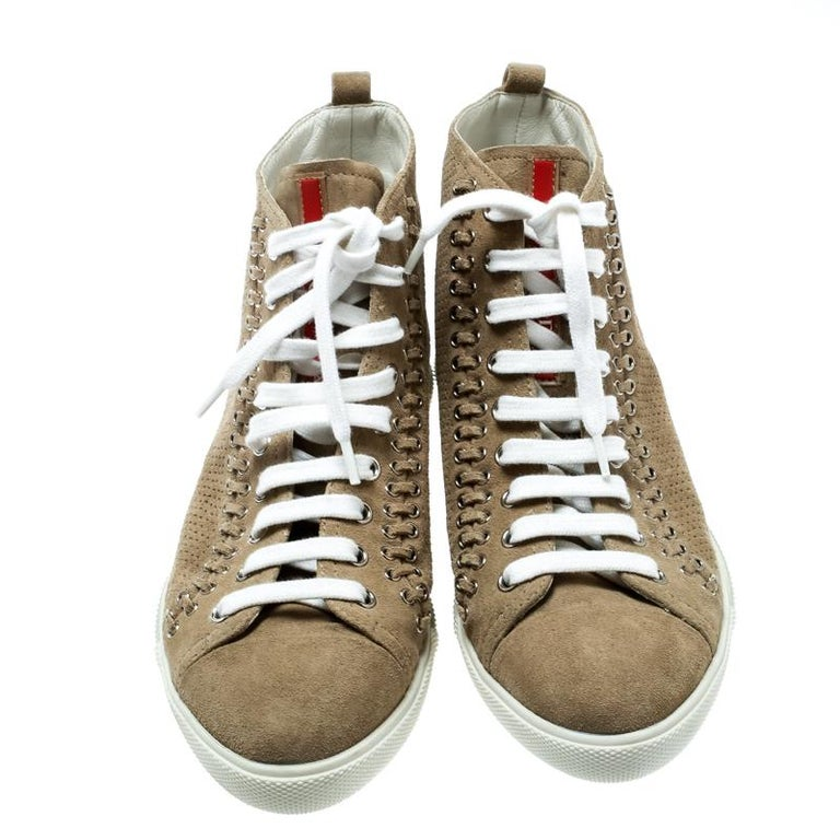 Essay your high-style in these super-stylish sneakers from the house of Prada! They are carefully crafted from suede and designed with lace-ups and eyelets. You are sure to receive both comfort and fashion when you choose this pair.  Includes: The