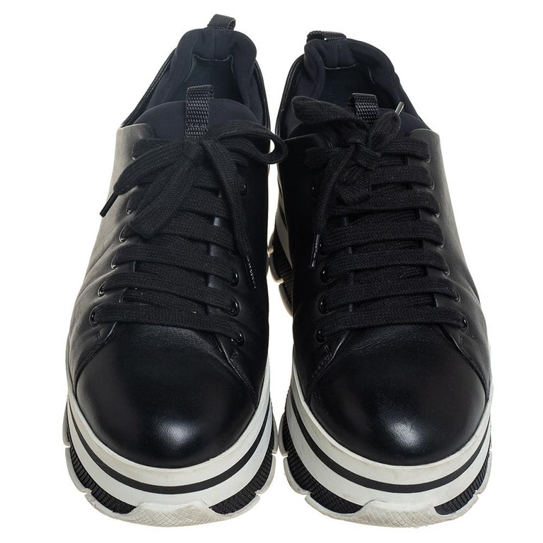 Project a stylish look every time you step out in these sneakers from Prada Sport. They are crafted from black leather, styled with lace-ups on the vamps, and elevated on striped platforms. They are equipped with comfortable leather-lined insoles