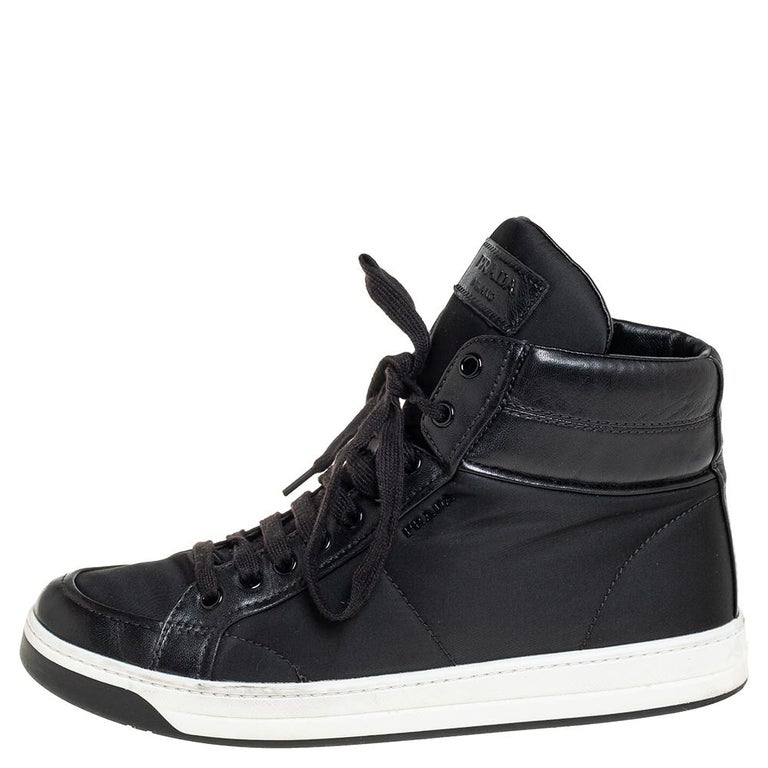 Comfort and style are brought together to form these stylish high-top sneakers by Prada Sport. They have been crafted from nylon as well as leather into a clean, minimal design. The highly reliable sneakers are secured with lace-ups and finished