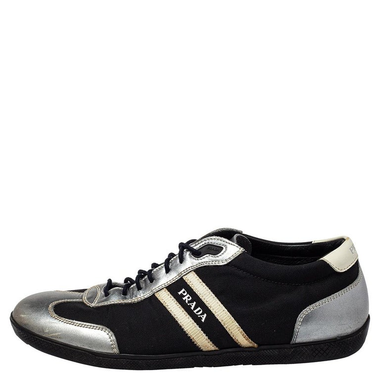 Fashioned in a low-top silhouette, these Prada Sport sneakers feature a silver laminated leather and black nylon body and come with round toes. Completed with lace-ups and logo details on the sides and the counters, this pair is set on rubber soles