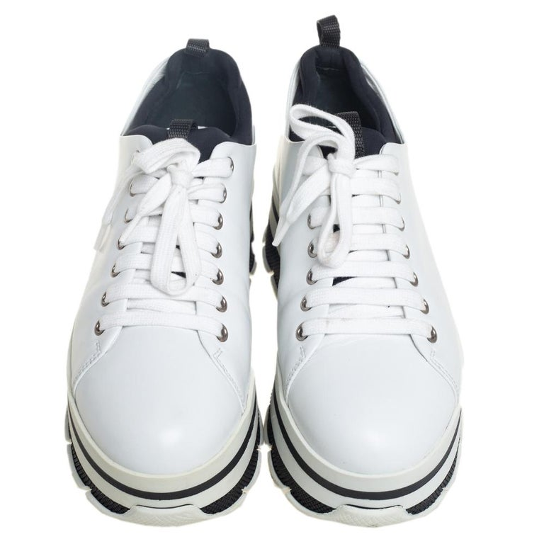 Project a stylish look every time you step out in these sneakers from Prada Sport. They are crafted from white leather, styled with lace-ups on the vamps, and elevated on striped platforms. They are equipped with comfortable leather-lined insoles