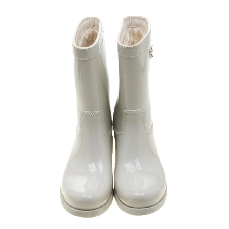 Enjoy the rain in style with these rain boots by Prada. Made from PVC, these cool white boots feature stitch detailed design and the Prada logo plaque in silver-tone. The interior is lined in fabric.  Includes: Original Dustbag