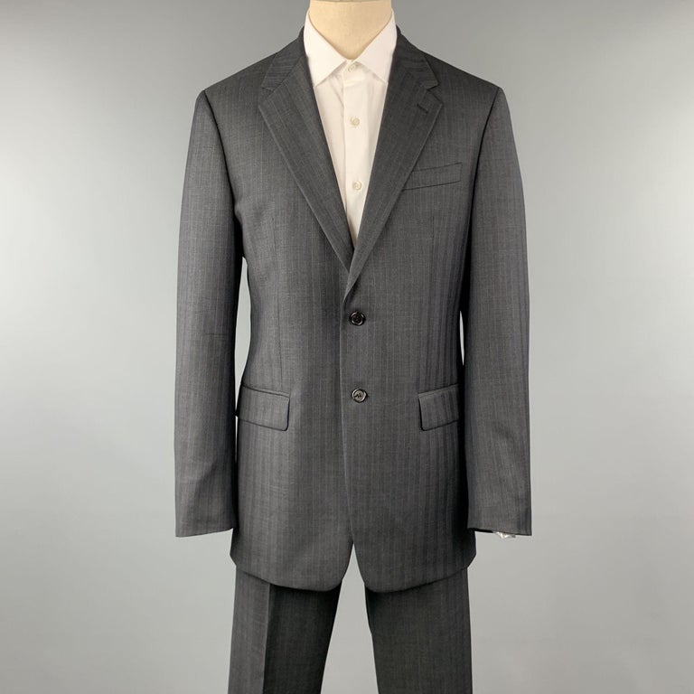 PRADA suit comes in a charcoal stripe wool and includes a single breasted, two button sport coat with notch lapel and matching front trousers. Made in Italy.  Pre-Owned Condition. Marked: 52 L  Measurements:  -Jacket Shoulder: 19 in.  Chest: 42 in.