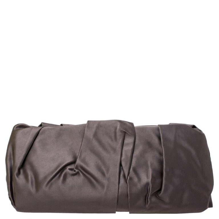 The perfect accessory on a night out, this Prada Raso clutch is elegant and stylish. The pleated satin exterior features brand detailing in gold-tone hardware. This clutch comes with a top push-lock closure that opens up to a satin-lined interior