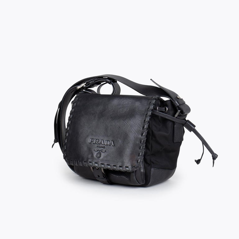 Black Tessuto Calf leather Prada crossbody bag with  - Silver-tone hardware - Single flat shoulder strap - Black interior lining - Black leather trim - Single interior zip pocket and drawstring closure at top  Overall Preloved Condition: Very