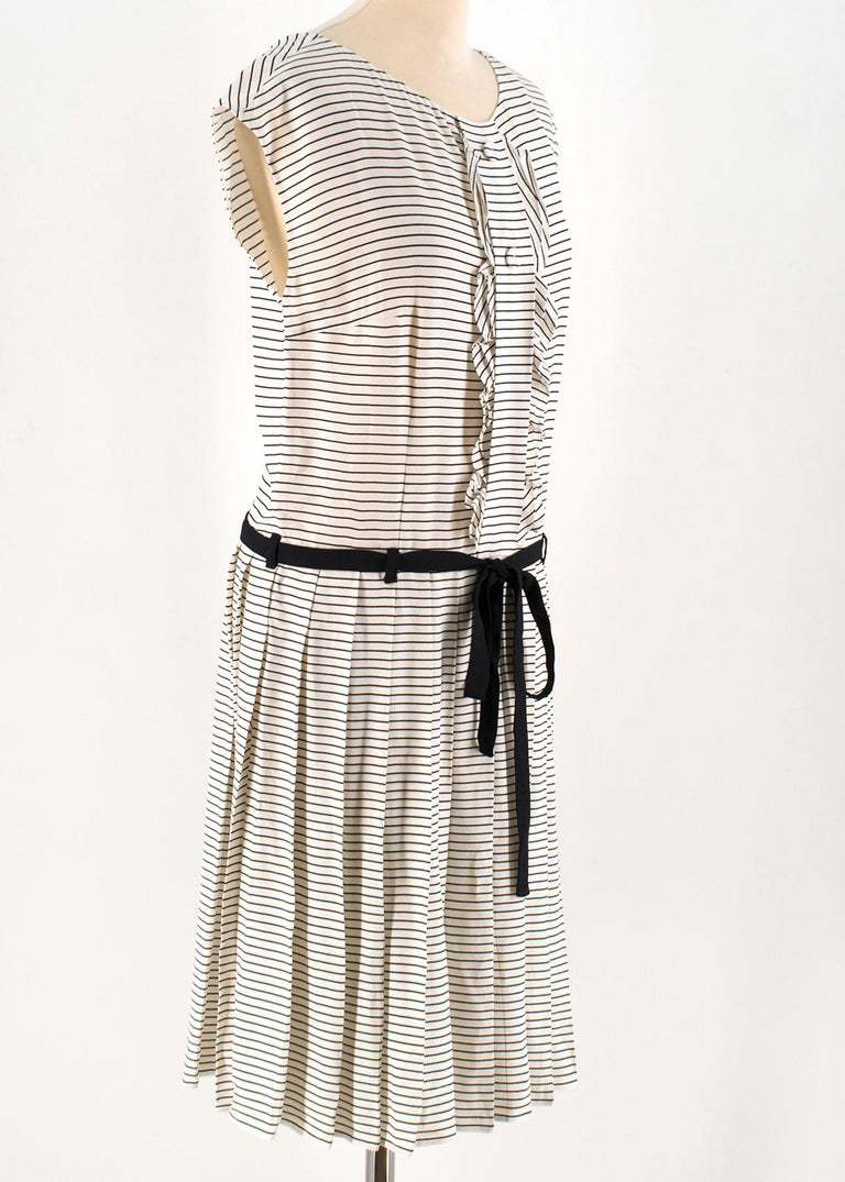 Prada Tie-Waist Striped Crepe Dress  -Cream and black striped, mid-weight crepe  -Round neck, capped sleeves  -Decorative placket and two buttons, ruffle-trimmed edges  -Drop waist, black crepe waist tie  -Pleated skirt  -Centre-back concealed zip