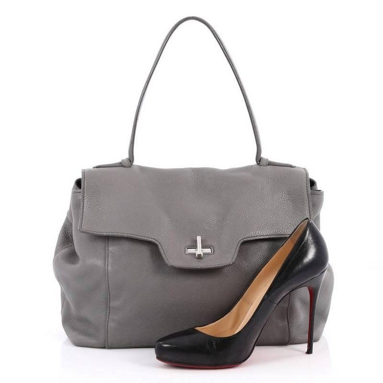 This authentic Prada Toro Top Handle Satchel Vitello Daino Large is a gorgeous and practical bag ideal for everyday use. Crafted from grey vitello daino leather, this sophisticated bag features flat leather top handle, exterior back zip pocket, slip