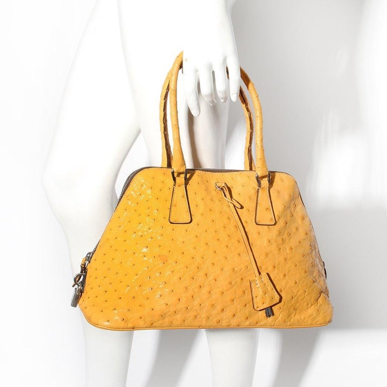 Prada Leather Trapazoid Handbag  Made in Italy  Mustard yellow color Ostrich leather  Small double handles at top of tote  Flat bottom  Silver tone lock hardaware Lock is stamped Prada  Attached silver tone keys for lock  Lined with green Prada logo