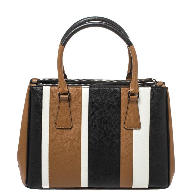 Feminine in shape and grand on design, this Double Zip tote by Prada will be a loved addition to your closet. It has been crafted from leather in tricolor stripes and styled minimally with silver-tone hardware. It comes with two top handles, two zip