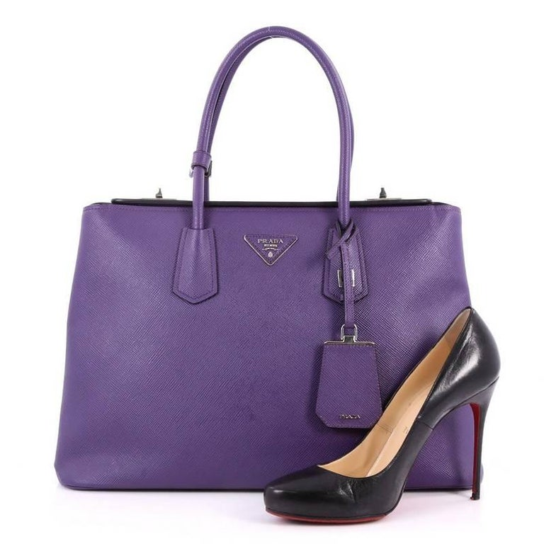 This authentic Prada Turnlock Twin Tote Saffiano Leather Medium is perfect to carry around everyday . Crafted from purple saffiano leather, this tote features dual-rolled leather handles, angular silhouette, inverted triangle Prada logo, side snap