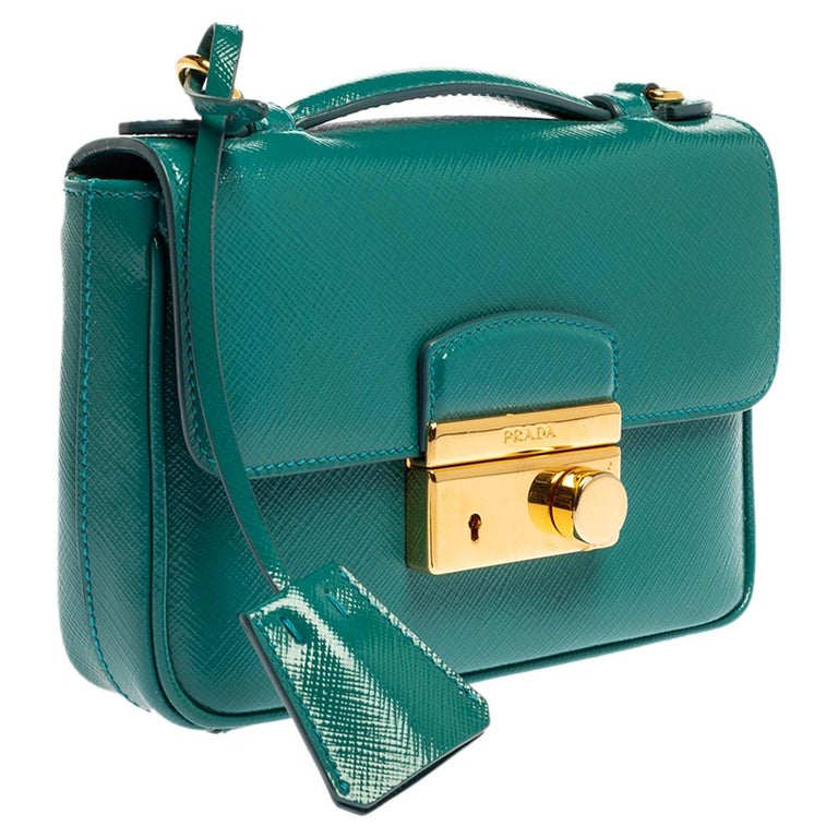 This bag exhibits Prada's exquisite approach to design. Beautiful Saffiano Vernic leather has been used to craft this bag. It comes in a turquoise hue and features a front flap with gold-tone closure. It opens to a nylon interior with enough space