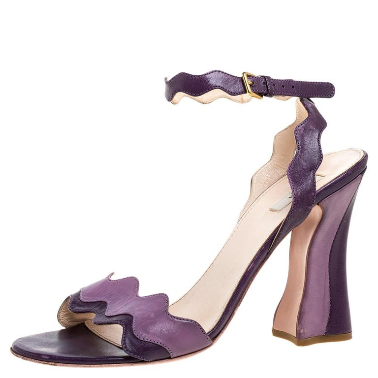 These sandals from Prada are a perfect blend of fashion and comfort! These two-toned purple sandals are crafted from leather and feature an open-toe silhouette with wavy straps. They come equipped with leather-lined insoles, ankle straps, 10.5 cm