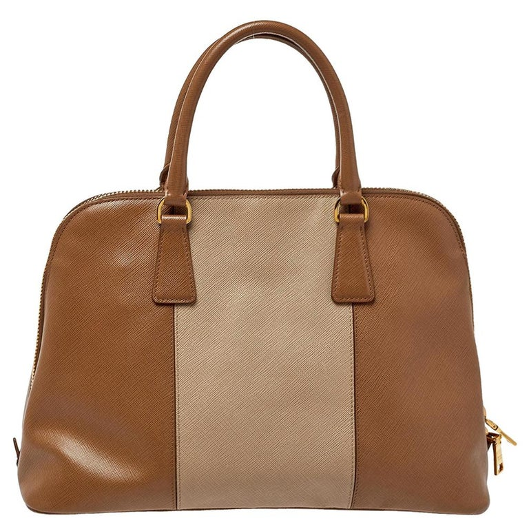 This stunning Promenade tote is high on appeal and style. Dazzling in classy beige shades, the two-tone bag is crafted from Saffiano leather and features two rolled handles. The zip closure leads way to a fabric interior with enough space for your