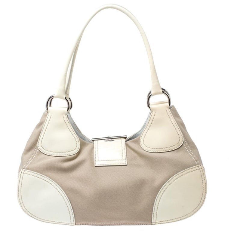 This white Prada bag is effortlessly stylish. Crafted from leather and canvas, it is held by dual handles, comes with buckle closure, fabric-lined interior with a zip pocket and enough space to carry your essentials. It is finished with silver-tone