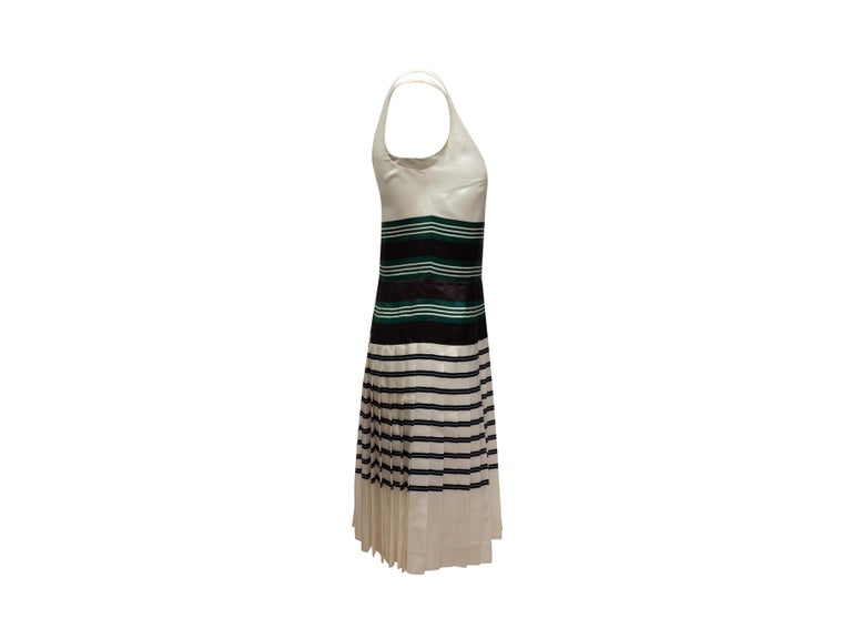 Product details: White, black, and dark green sleeveless dress by Prada. Striped print throughout. Scoop neck. Pleated skirt. 31