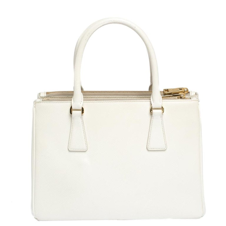 Feminine in shape and grand in design, this Double Zip tote by Prada will be a loved addition to your closet. It has been crafted from Saffiano Lux leather and styled minimally with gold-tone hardware. It comes with two top handles, two zip