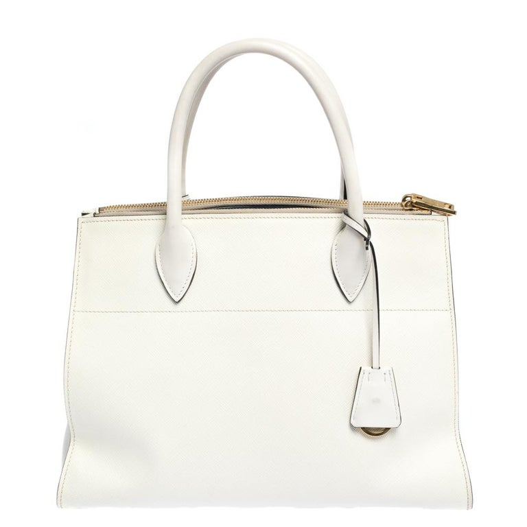 Prada's Paradigme tote exudes appeal through a structured shape and minimal detailing. Crafted from Saffiano Lux leather, the tote in white has two handles, a shoulder strap, triangular side gussets and a spacious interior. Make it yours