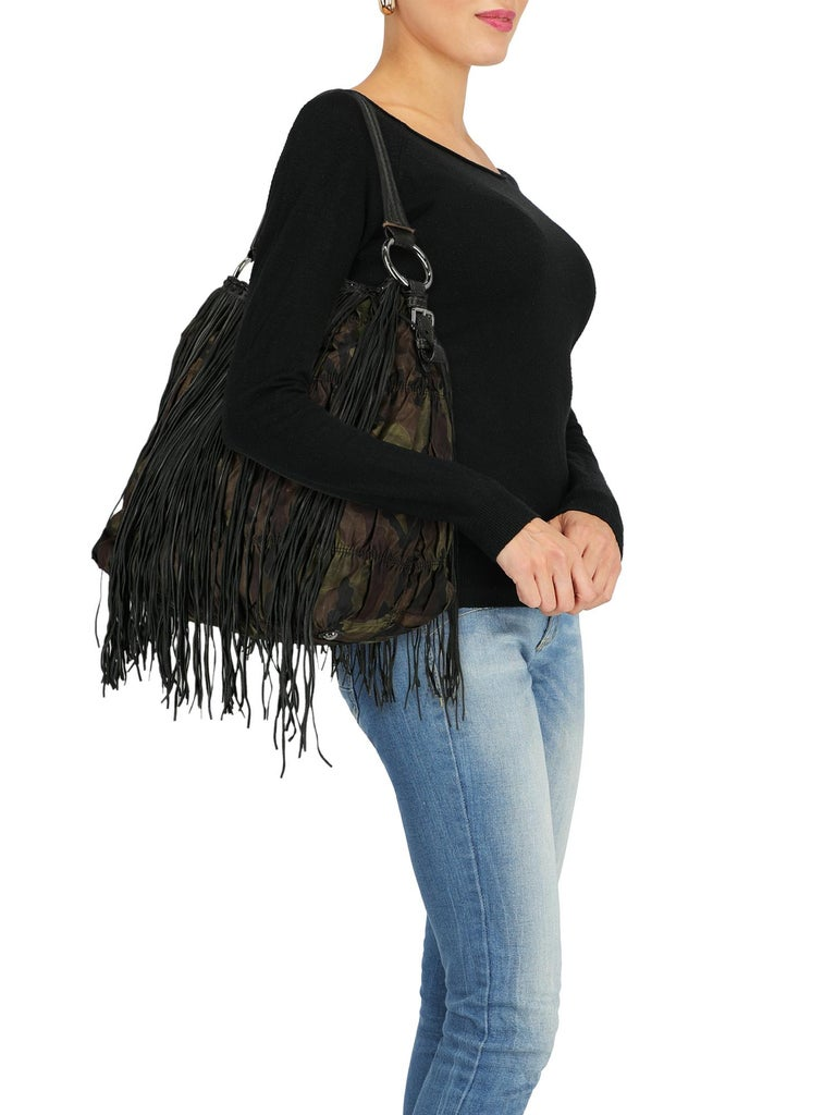 Hobo bag, fabric, camouflage print, internal logo, magnetic closure, silver-tone hardware, internal zipped pocket, double smartphone pocket, fringe embellishment, day bag.  Includes: - Dust bag  Product Condition: Very Good Lining: visible glue