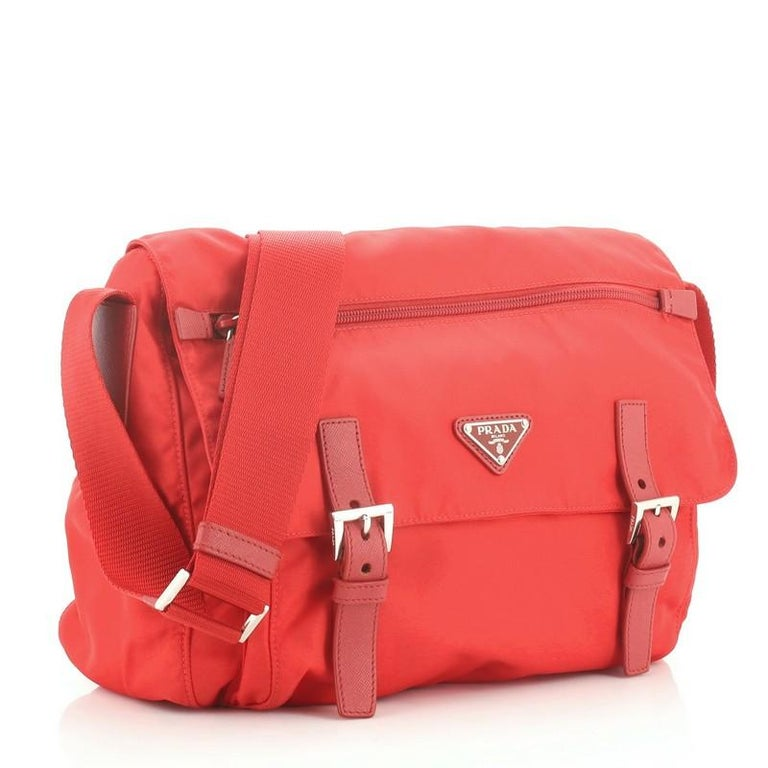 This Prada Zip Buckle Messenger Bag Tessuto Medium, crafted in red tessuto, features an adjustable shoulder strap, exterior front zip pocket on flap, exterior back zip pocket, and silver-tone hardware. Its buckle closure opens to a red fabric