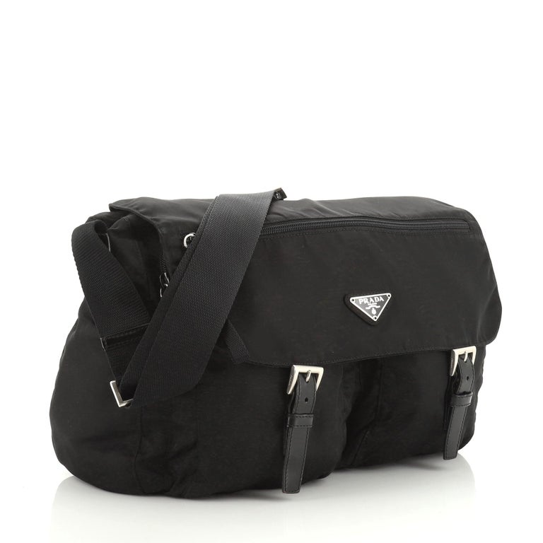 This Prada Zip Buckle Messenger Bag Tessuto Medium, crafted from black tessuto, features an adjustable shoulder strap, exterior front zip pocket on flap, two zip pockets under flap, and silver-tone hardware. Its flap and zip closures open to a black