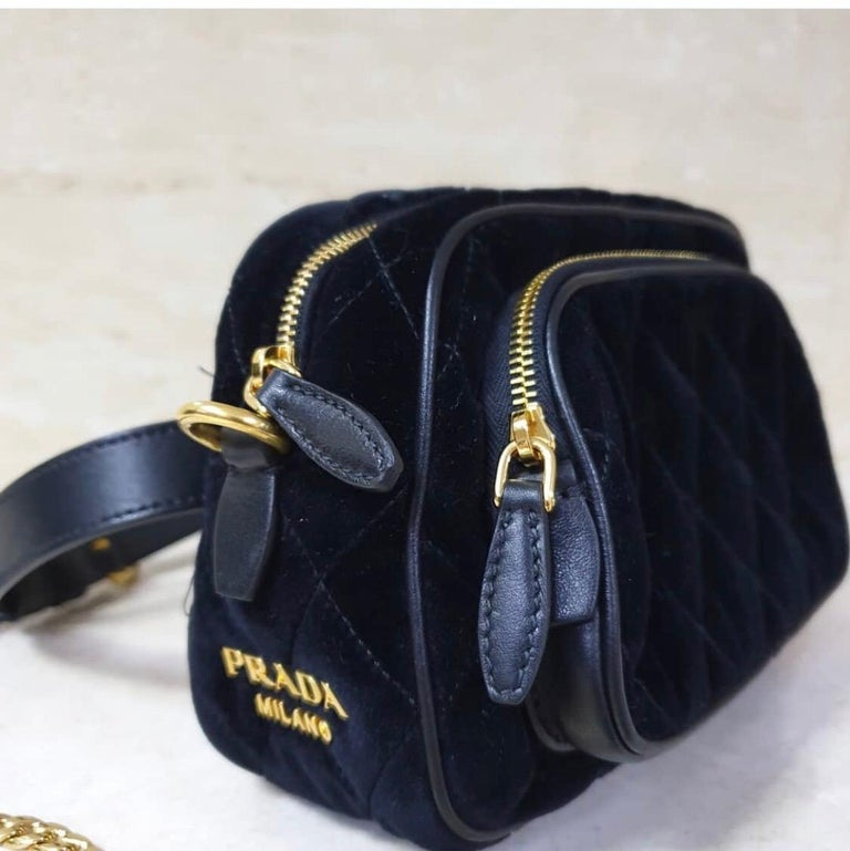Prada convertible bag in velvet and leather with golden hardware Interchangeable straps for use as a belt bag or crossbody bag. Removable chain shoulder strap. Zip-around top closure Exterior, hanging tassels with golden rings. Zip-around front