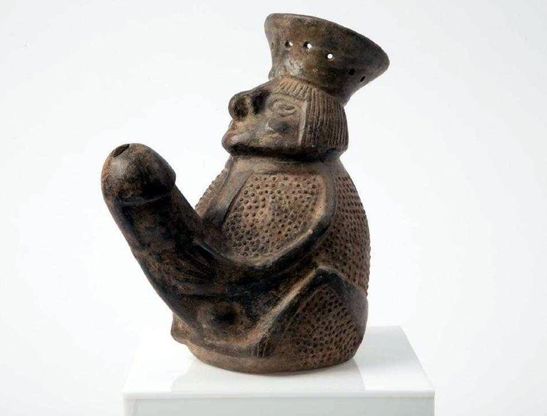 A striking homomorphic black pot, from the Chimu Culture (8th-15th century AD) along the Northern Coast of the nowadays Peru, of a jug form as a man with an exaggerated phallus. Well molded face and expertly outlined limbs. The surface is decorated